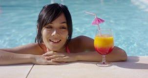 Glückliche junge Frau, die ein großes tropisches Cocktail mustert stock video