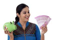 Glückliche junge Frau, die ein Sparschwein und Anmerkungen der indischen Rupie hält Lizenzfreie Stockfotografie