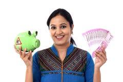Glückliche junge Frau, die ein Sparschwein und Anmerkungen der indischen Rupie hält Stockbild