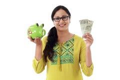 Glückliche junge Frau, die ein Sparschwein und Anmerkungen der indischen Rupie hält lizenzfreie stockfotos