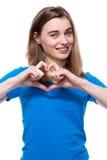 Glückliche junge Frau, die eine Herzgeste macht Lizenzfreie Stockfotos