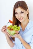 Glückliche junge Frau, die einen frischen Salat isst Stockfotos