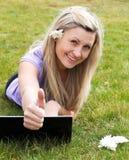 Glückliche junge Frau, die einen Laptop in einem Park verwendet Stockbild