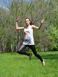 Glückliche junge Frau, die in einer Luft springt Lizenzfreies Stockbild