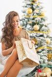 Glückliche junge Frau, die Einkaufstasche nahe Weihnachtsbaum untersucht Stockfotografie