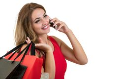 Glückliche junge Frau, die Einkaufstaschen und Handy über weißem Hintergrund hält lizenzfreies stockbild