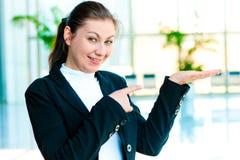 Glückliche junge Frau, die etwas auf der Palme Ihrer Hand und Punkte ein Finger an ihr hält Lizenzfreies Stockbild