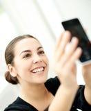 Glückliche junge Frau, die für ein selfie aufwirft stockbild