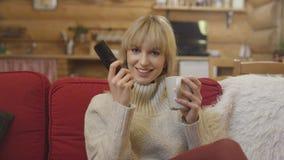 Glückliche junge Frau, die Fernbedienung verwendet, um Kanal beim zu Hause sitzen zu ändern Stockfotos