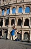 Glückliche junge Frau, die gegen Kolosseum in Rom springt stockfotos