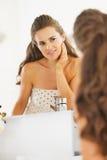 Glückliche junge Frau, die Gesichtshautzustand im Badezimmer überprüft Stockbild