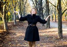 Glückliche junge Frau, die Hände im Herbstpark anhebt Stockfoto