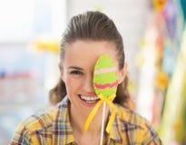 Glückliche junge Frau, die handgemachtes dekoratives Ei hält Lizenzfreie Stockbilder