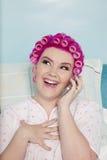 Glückliche junge Frau, die am Handy mit Haarlockenwicklern spricht lizenzfreies stockfoto
