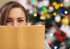 Glückliche junge Frau, die hinter Buch nahe Weihnachtsbaum sich versteckt stockfoto