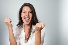 Glückliche junge Frau, die ihrem Erfolg zujubelt lizenzfreie stockfotos