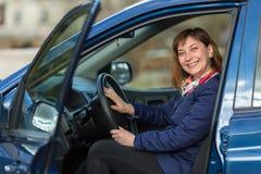 Glückliche junge Frau, die ihren Neuwagen fährt liebhaberei stockbilder