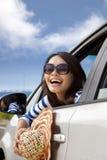 Glückliche junge Frau, die im Auto sitzt Stockbild