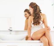 Glückliche junge Frau, die im Badezimmer sitzt und im Spiegel schaut stockbilder