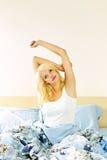 Glückliche junge Frau, die im Bett aufwacht Lizenzfreie Stockfotografie