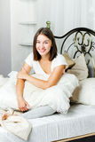 Glückliche junge Frau, die im Bett sitzt Lizenzfreies Stockfoto