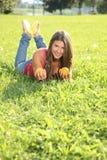 Glückliche junge Frau, die im Gras mit Orangen liegt Lizenzfreie Stockfotos