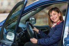 Glückliche junge Frau, die im Neuwagen sitzt liebhaberei stockfotografie