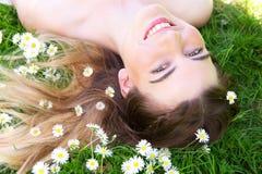 Glückliche junge Frau, die im Park mit Blumen lächelt Stockfoto