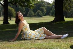 Glückliche junge Frau, die im Parksommersonnenschein sich bräunt Stockfotos