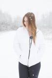 Glückliche junge Frau, die im Schnee steht Stockfotos
