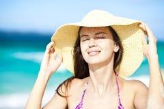 Glückliche junge Frau, die im Strohhut mit geschlossenen Augen auf dem Strand lächelt Lizenzfreies Stockbild