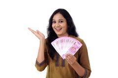Glückliche junge Frau, die Inder 2000 Rupienanmerkungen hält Stockbilder