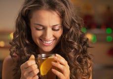 Glückliche junge Frau, die Ingwertee mit Zitrone trinkend genießt Lizenzfreies Stockbild