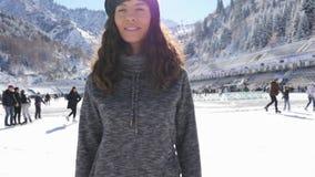 Glückliche junge Frau, die Kamera, Eislaufmädchen an der Eisbahn betrachtet stock video