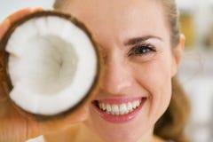 Glückliche junge Frau, die Kokosnussstück vor Auge hält Lizenzfreie Stockfotografie