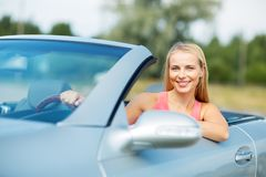 Glückliche junge Frau, die konvertierbares Auto fährt stockfoto
