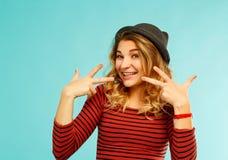 Glückliche junge Frau, die laut über blauem Hintergrund lacht Lizenzfreie Stockfotografie