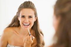 Glückliche junge Frau, die Lipgloss im Badezimmer anwendet Stockfotografie