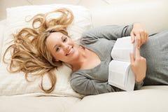 Glückliche junge Frau, die mit Buch liegt lizenzfreies stockfoto