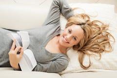 Glückliche junge Frau, die mit Buch liegt Stockfotografie