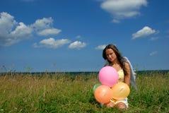 Glückliche junge Frau, die mit bunten Ballonen stationiert stockfoto