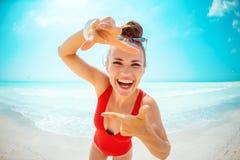 Glückliche junge Frau, die mit den Händen auf Seeküste gestaltet lizenzfreie stockfotos
