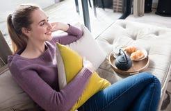 Glückliche junge Frau, die mit europäischem Frühstück für entspannenden Morgen sitzt lizenzfreie stockbilder