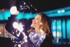 Glückliche junge Frau, die mit feenhaften Lichtern am Winterabend herein spielt stockbilder