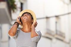 Glückliche junge Frau, die mit Handy lacht Stockfotografie