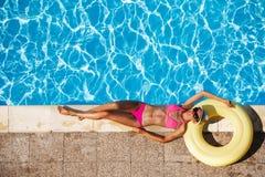 Glückliche junge Frau, die nahe dem Swimmingpool stillsteht Lizenzfreies Stockbild