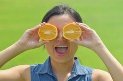Glückliche junge Frau, die orange Scheiben hält Stockbild