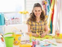 Glückliche junge Frau, die Ostern-Dekoration macht stockbild