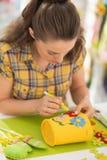 Glückliche junge Frau, die Ostern-Dekoration macht stockfoto