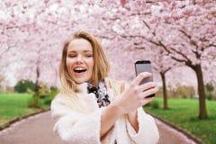 Glückliche junge Frau, die am Park sich fotografiert Lizenzfreies Stockfoto